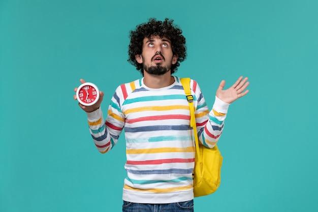 Vista frontal do estudante do sexo masculino com mochila amarela segurando relógios na parede azul clara