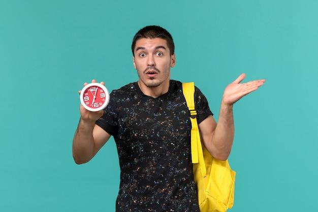 Vista frontal do estudante do sexo masculino na mochila de camiseta amarela escura segurando relógios na parede azul clara