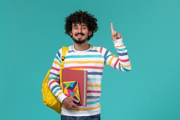 Vista frontal do estudante do sexo masculino usando mochila amarela segurando arquivos e o caderno na parede azul