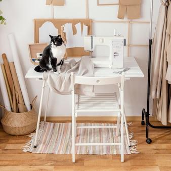 Vista frontal do estúdio de alfaiataria com máquina de costura e gato