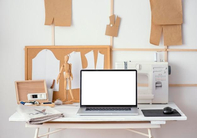 Vista frontal do estúdio de alfaiataria com máquina de costura e laptop