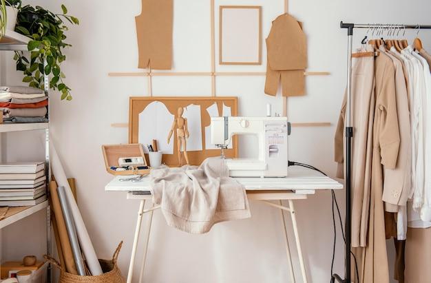 Vista frontal do estúdio de alfaiataria com máquina de costura e roupas
