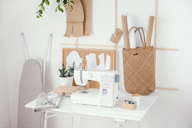 Vista frontal do estúdio de alfaiataria com máquina de costura na mesa
