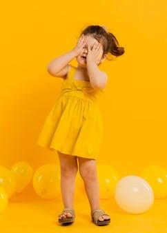 Vista frontal do filho bonito posando com balões