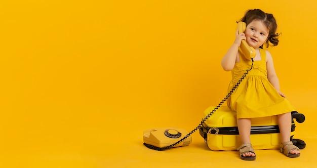 Vista frontal do filho bonito posando com telefone e bagagem
