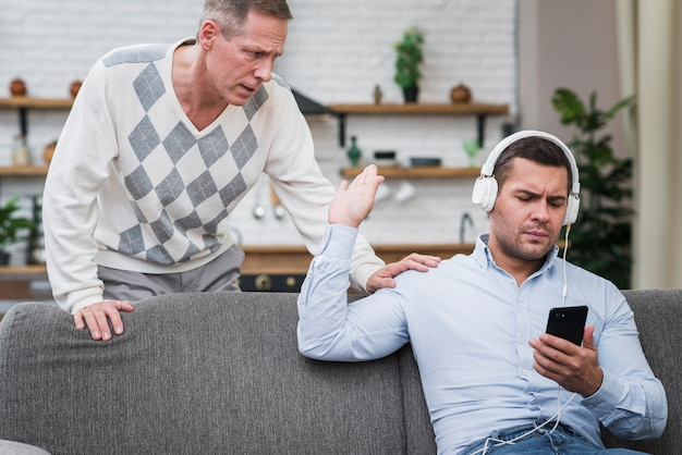 Vista frontal do filho interromper seu pai falando