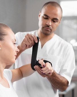 Vista frontal do fisioterapeuta masculino envolvendo o pulso da mulher