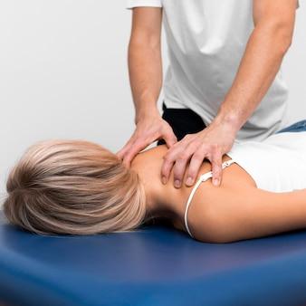 Vista frontal do fisioterapeuta massageando as costas da mulher para a dor