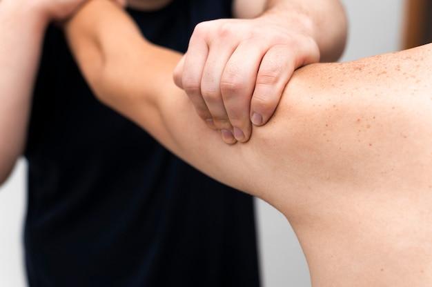 Vista frontal do fisioterapeuta massageando o braço do homem