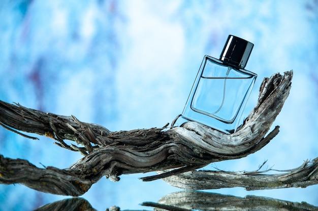 Vista frontal do frasco de colônia em um galho de árvore podre em fundo azul claro