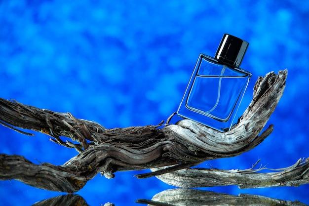 Vista frontal do frasco de colônia retangular em galho de árvore podre em azul