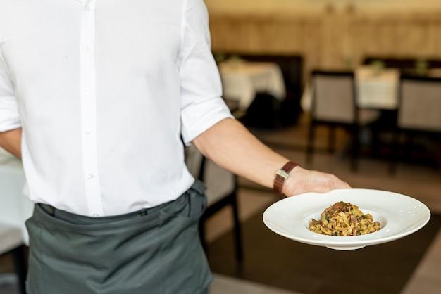 Vista frontal do garçom segurando um prato com macarrão