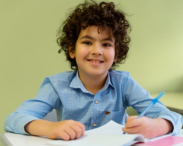 Vista frontal do garotinho sorridente na classe da escola