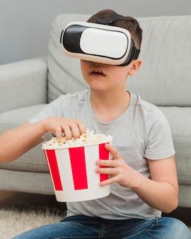 Vista frontal do garoto assistindo filme com fone de ouvido de realidade virtual e pipoca