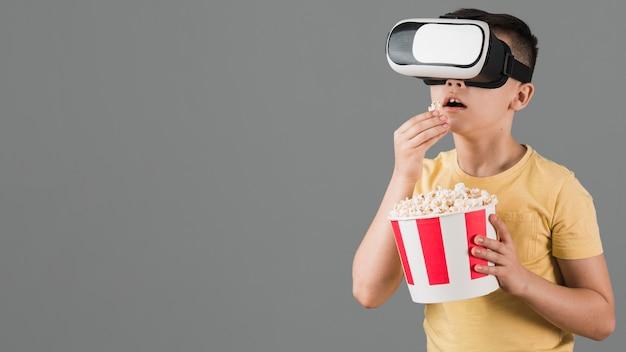 Vista frontal do garoto assistindo filme no fone de ouvido da realidade virtual e comendo pipoca
