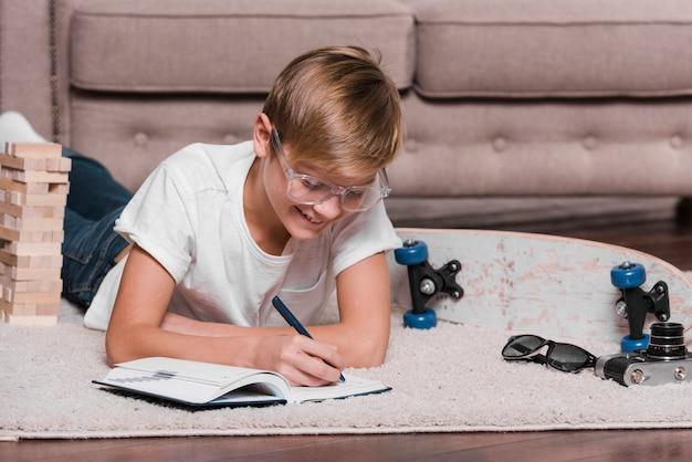 Vista frontal do garoto escrevendo em uma agenda