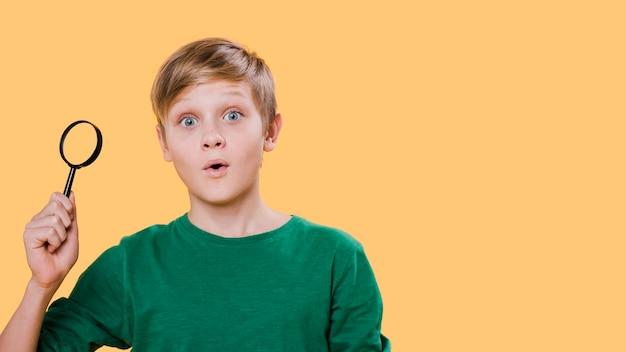 Vista frontal do garoto segurando a lupa com espaço de cópia
