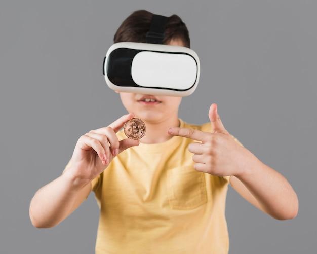 Vista frontal do garoto segurando bitcoin enquanto usava fone de realidade virtual