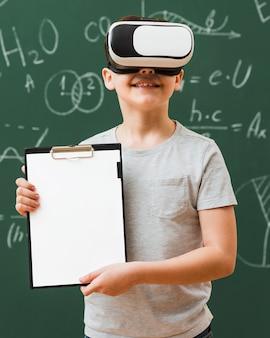 Vista frontal do garoto segurando o bloco de notas enquanto usava fone de realidade virtual