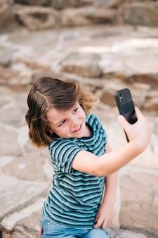 Vista frontal do garoto tomando uma selfie