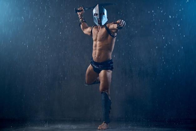 Vista frontal do gladiador romano molhado gritando com raiva no capacete de ferro, segurando a espada. espartano musculoso sem camisa com armadura, pulando durante o ataque em um mau tempo chuvoso. conceito de antigo guerreiro.
