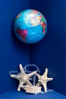 Vista frontal do globo da terra e estrela do mar com plástico