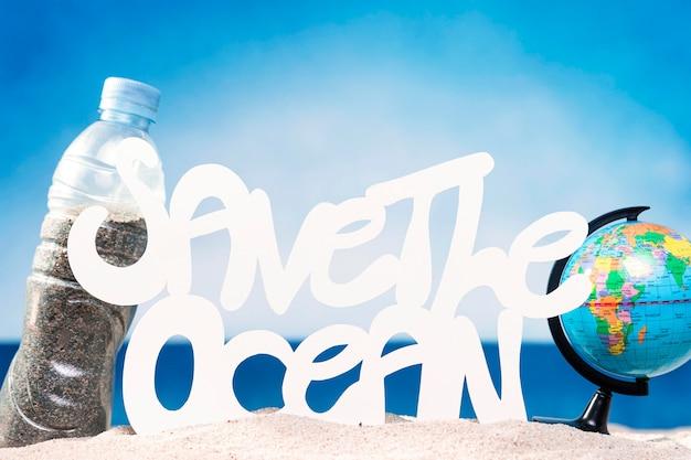 Vista frontal do globo e garrafa de plástico com areia na praia
