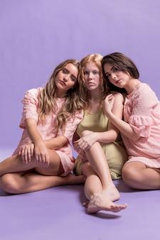 Vista frontal do grupo de mulheres, abraçando-se como um sinal de empoderamento
