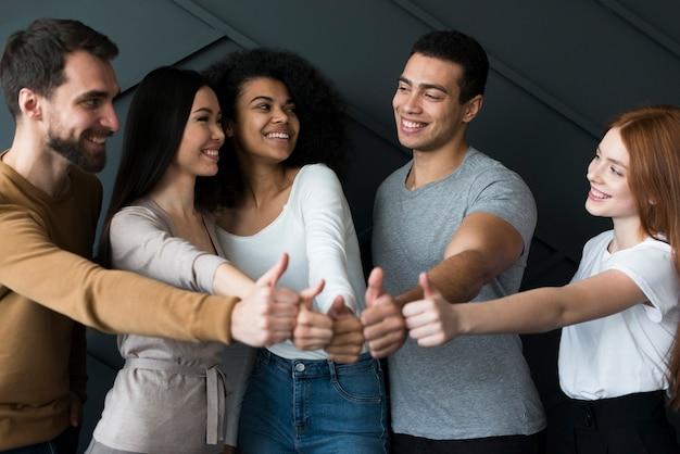 Vista frontal do grupo de pessoas com polegares para cima