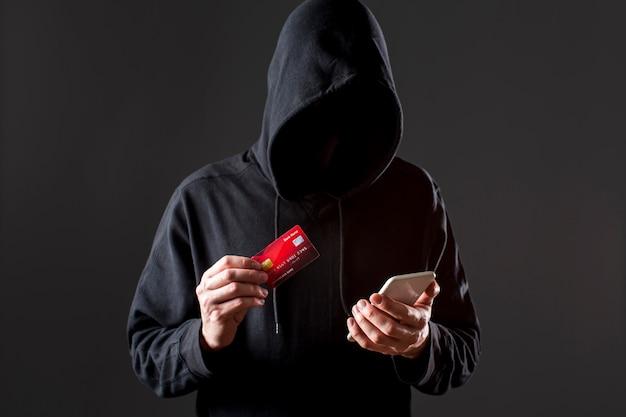 Vista frontal do hacker masculino segurando o smartphone e cartão de crédito