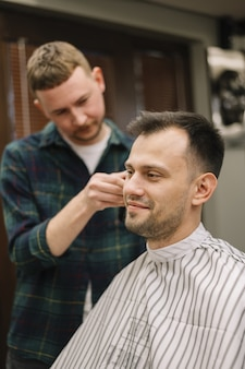 Vista frontal do hairstilyst dando um corte de cabelo