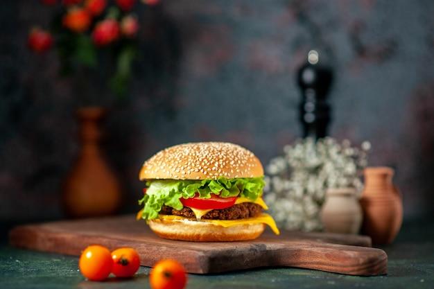 Vista frontal do hambúrguer de carne com tomates frescos em fundo escuro