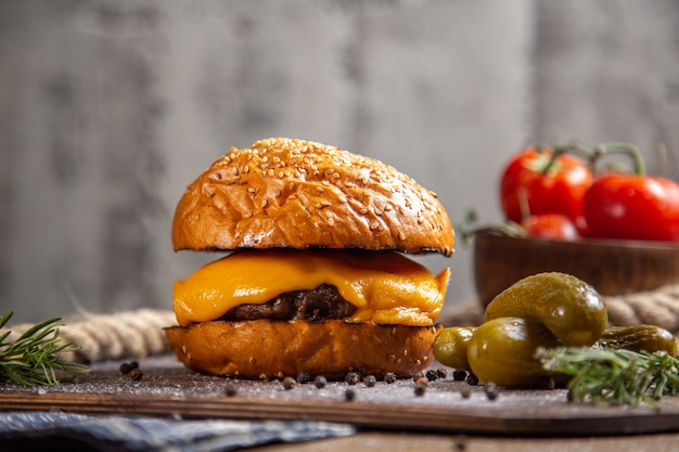 Vista frontal do hambúrguer de carne de queijo com pickles verdes e tomates na mesa de madeira