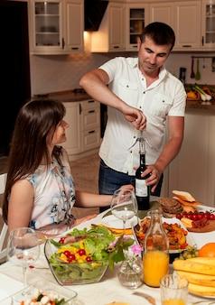 Vista frontal do homem abrindo uma garrafa de vinho na mesa de jantar