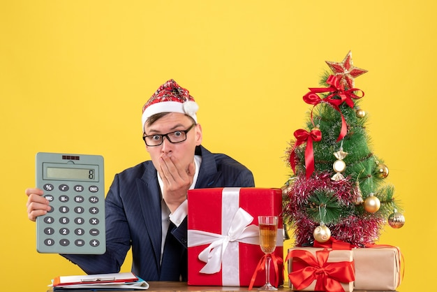 Vista frontal do homem admirado segurando uma calculadora, sentado à mesa perto da árvore de natal e presentes em amarelo