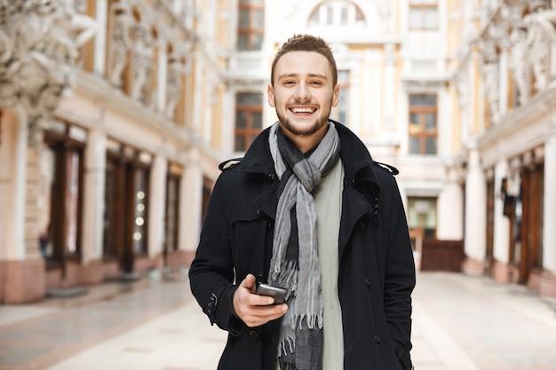 Vista frontal do homem alegre, segurando o telefone e olhando em linha reta.