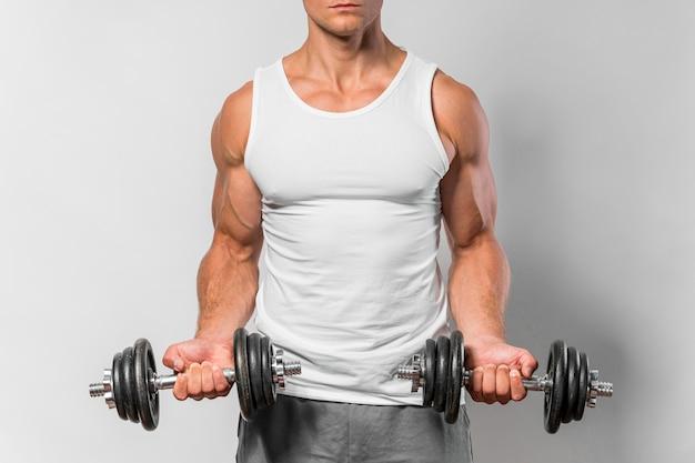 Vista frontal do homem apto com camiseta regata malhando com pesos