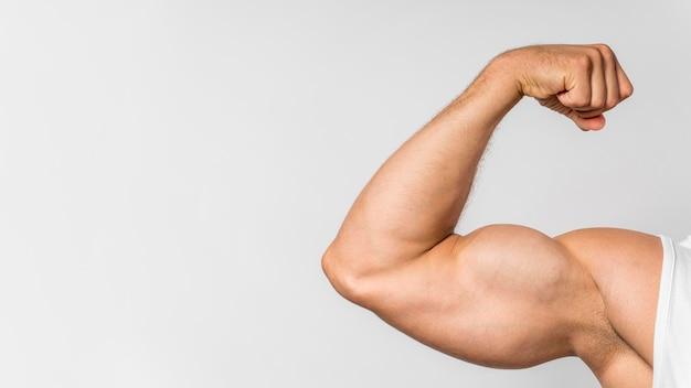 Vista frontal do homem apto mostrando bíceps com espaço de cópia