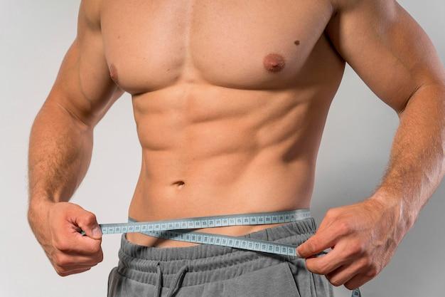 Vista frontal do homem apto segurando a fita métrica em volta da cintura