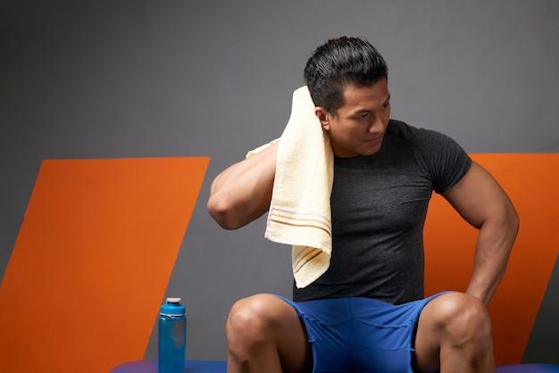 Vista frontal do homem atlético, limpando a cabeça com a toalha relaxante após o treino