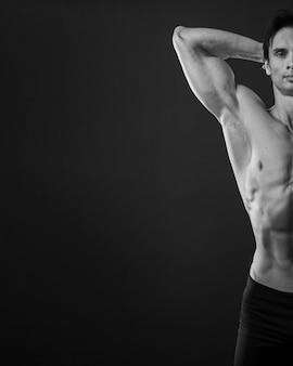 Vista frontal do homem atlético, mostrando o bíceps em preto e branco