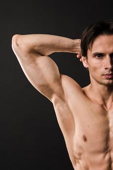 Vista frontal do homem atlético, mostrando o bíceps