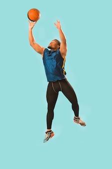 Vista frontal do homem atlético no desgaste do ginásio jogando basquete