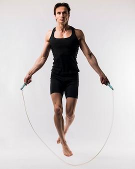 Vista frontal do homem atlético, pular corda