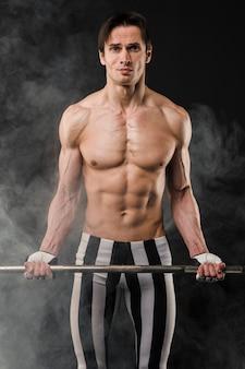 Vista frontal do homem atlético sem camisa, segurando o conjunto de peso