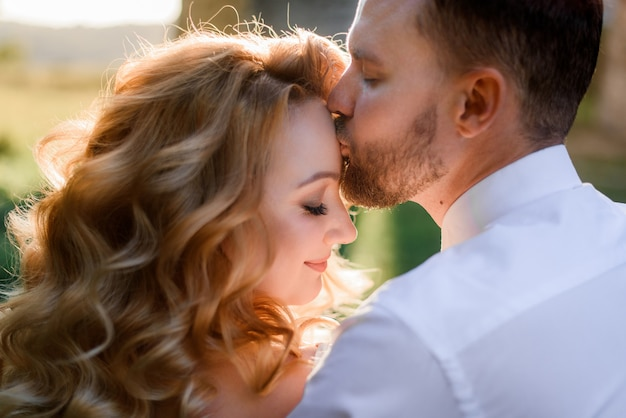 Vista frontal do homem barbudo está beijando menina loira com penteado e maquiagem na testa ao ar livre no dia ensolarado