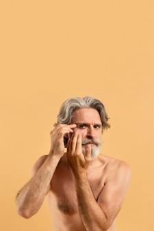 Vista frontal do homem barbudo mais velho, apontando rugas com espaço de cópia