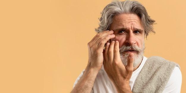 Vista frontal do homem barbudo mais velho não está feliz com rugas