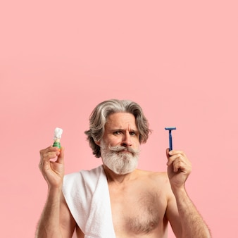Vista frontal do homem barbudo sênior com espuma e lâmina de barbear