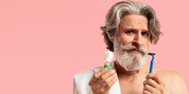 Vista frontal do homem barbudo sênior com lâmina de barbear e espuma